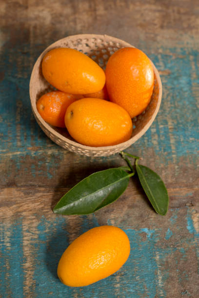 Delicious small citrus fruits orange kumquats close up on wooden table